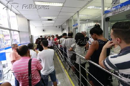 Pessoas na fila de agência da Caixa Econômica Federal