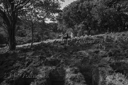 Coveiros carregam caixão no cemitério São Luiz (SP)
