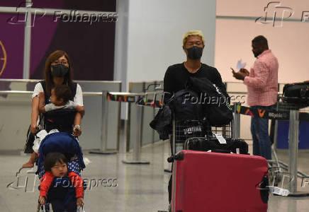 Turistas e funcionários do Aeroporto do Galeão usam máscaras