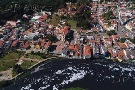 Vista de drone de moradias na margem do Rio Tietê poluído