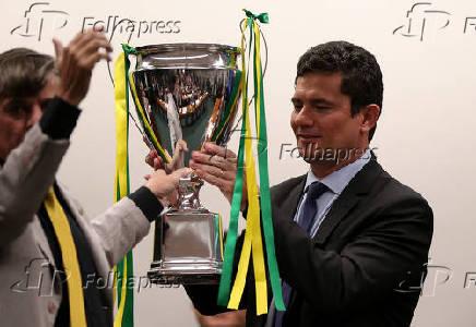 O deputado Boca Aberta entre troféu ao ministro Sergio Moro