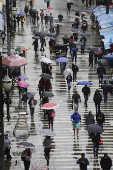 Pessoas se protegem do frio e da chuva no centro de SP