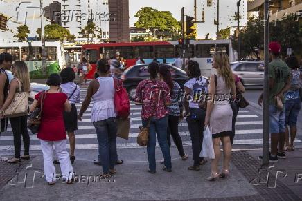 Pedestres aguardando para atravessar avenida