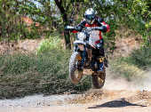 Man jumping with his scrambler type enduro motorbike on dirt track, rear view, Bangkok, Thailand