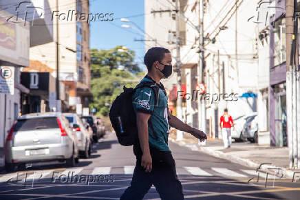 Rapaz com máscara de proteção realiza travessia em faixa de pedestre