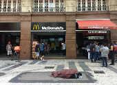 Homem dorme no calçadão da Barão de Itapetininga, em frente ao McDonald's